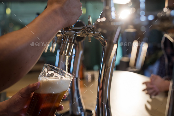 Cropped hands of bartender pouring beer - Stock Photo - Images