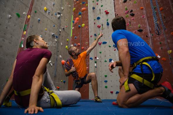 Male trainer guiding athletes in wall climbing at gym - Stock Photo - Images