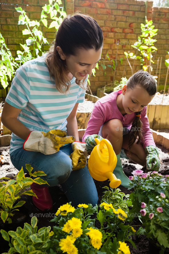 Smiling mother kneeling by girl watering plants - Stock Photo - Images