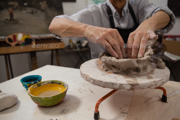 Mid-section of senior man molding clay - Stock Photo - Images