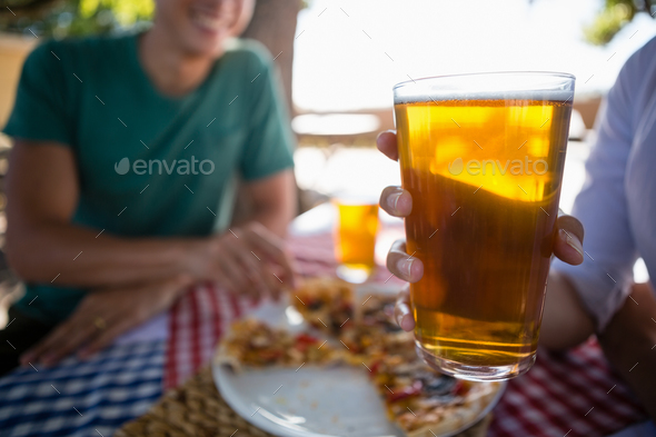 Cropped hand of woman with friend holding beer glass - Stock Photo - Images