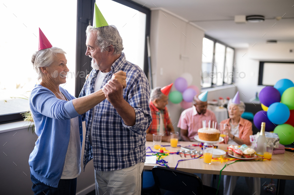 Smiling senior couple dancing by friends at party - Stock Photo - Images