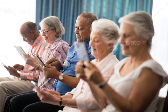 Smiling senior people using digital tablets while sitting on chairs - Stock Photo - Images