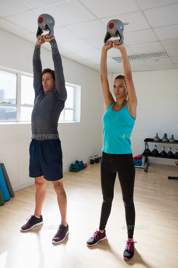 Trainer with athlete lifting kettlebells in gym - Stock Photo - Images