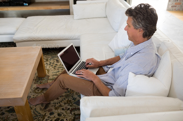 Man using laptop in living room - Stock Photo - Images