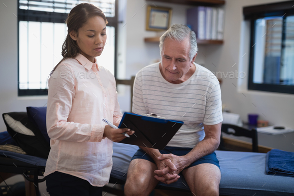 Female therapist showing clipboard to senior male patient sitting on bed - Stock Photo - Images