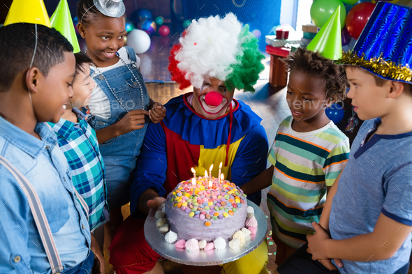 High angle view of children with clown standing by cake - Stock Photo - Images