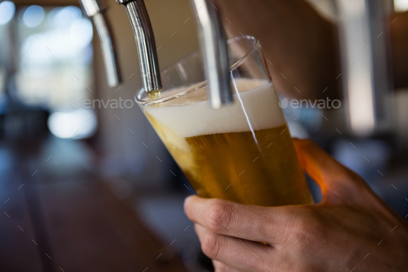 Cropped hand of bartender pouring beer from tap in glass - Stock Photo - Images