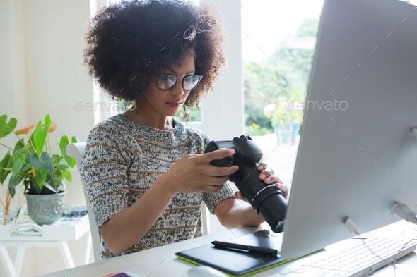 Graphic designer reviewing pictures on digital camera - Stock Photo - Images