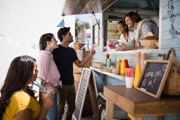Smiling waiter taking order from couple - Stock Photo - Images