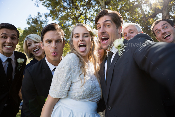 Happy couple posing with guests during wedding - Stock Photo - Images