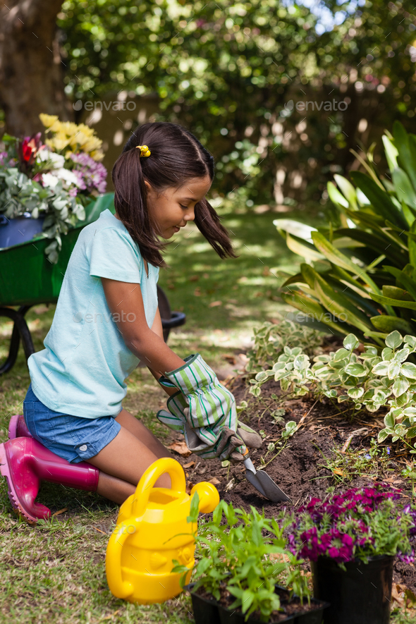 Side view of girl kneeling while digging soil with trowel - Stock Photo - Images