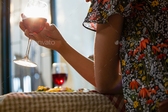 Midsection of woman holding wineglass - Stock Photo - Images