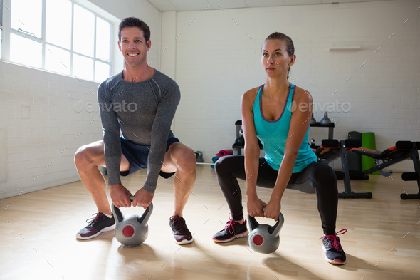 Athletes lifting kettlebells in health club - Stock Photo - Images