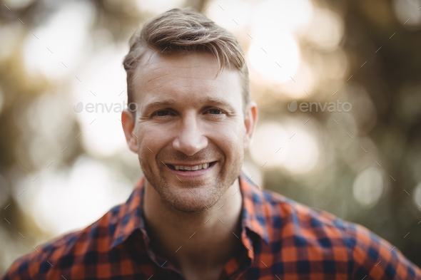 Portrait of smiling young man at farm - Stock Photo - Images