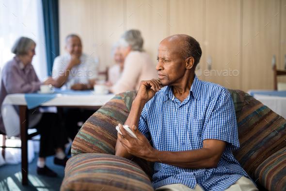 Thoughtful senior man holding mobile phone - Stock Photo - Images