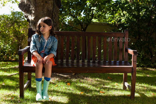 Girl wearing casual sitting on wooden bench - Stock Photo - Images