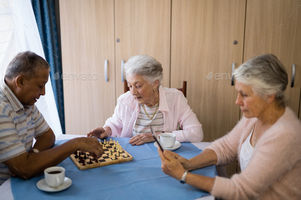 Senior friends playing chess and having coffee - Stock Photo - Images