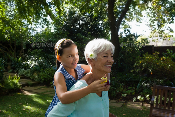 Smiling woman carrying granddaughter with flowers - Stock Photo - Images
