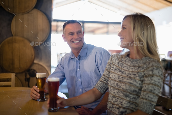 Couple interacting with each other while having beer in bar - Stock Photo - Images