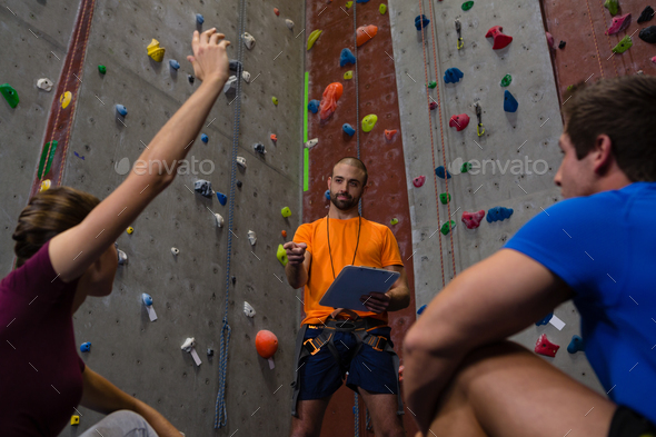 Low angle view of male trainer interacting with athletes sitting in gym - Stock Photo - Images