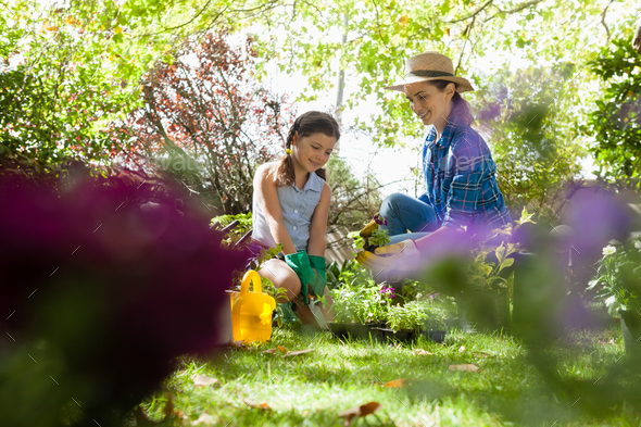 Smiling mother with daughter looking at potted plants - Stock Photo - Images