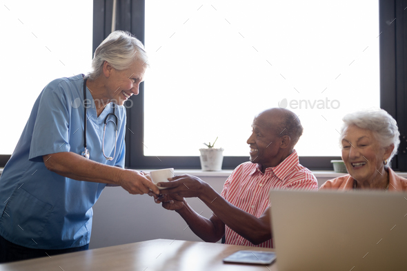 Smiling healthcare worker serving coffee to senior man sitting by friend - Stock Photo - Images