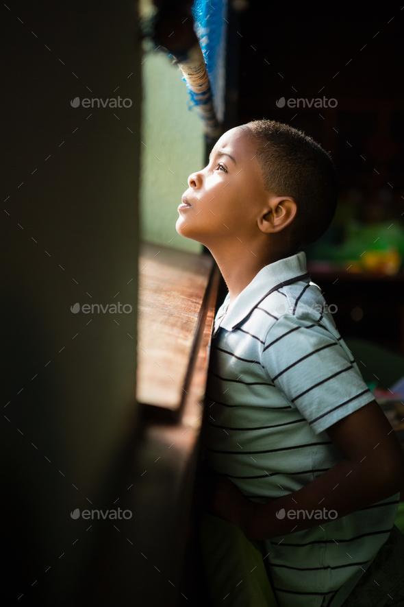 Thoughtful Boy Looking Through Window Stock Photo By Wavebreakmedia