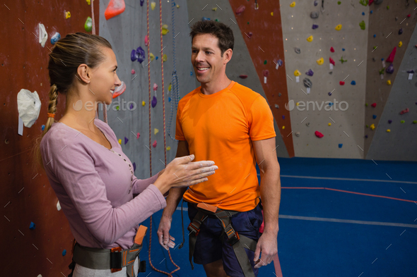 Female athlete talking to male trainer at health club - Stock Photo - Images
