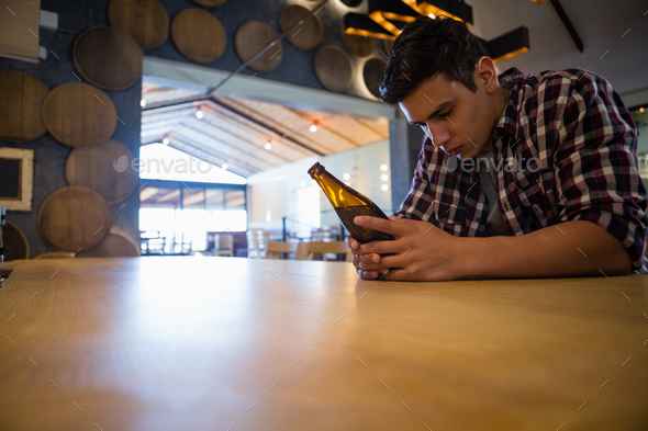 Sad man with beer bottle at bar - Stock Photo - Images