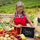 Happy woman holding slate with text at vegetable stall - PhotoDune Item for Sale