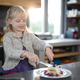Little girl cutting a fruit pancake with a fork and knife - PhotoDune Item for Sale