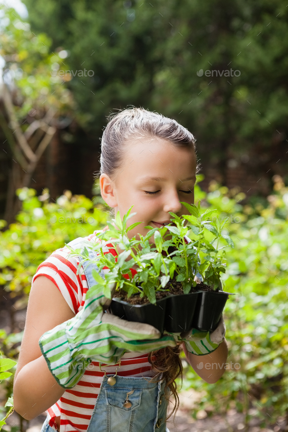Girl smelling plants with eyes closed - Stock Photo - Images