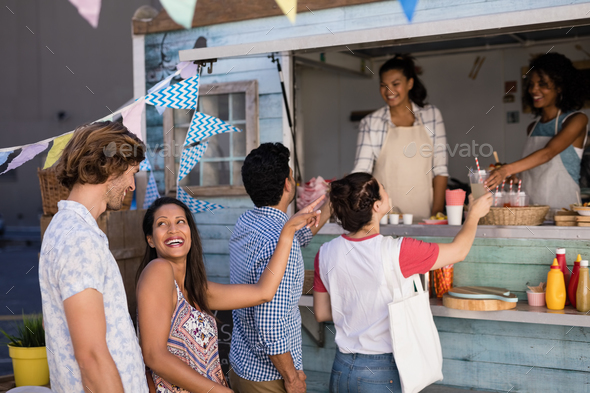 Waitress giving juice to customer at counter - Stock Photo - Images