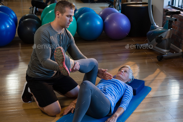 Male physiotherapist helping patient in performing exercise with resistance band - Stock Photo - Images