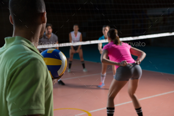 Male player playing volleyball with teammates - Stock Photo - Images
