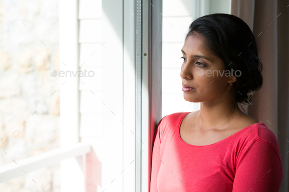 Thoughtful young woman looking through window - Stock Photo - Images