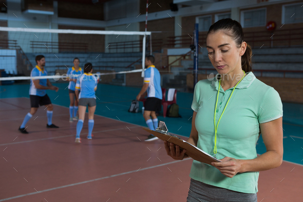 Coach holding clipboard at volleyball court - Stock Photo - Images
