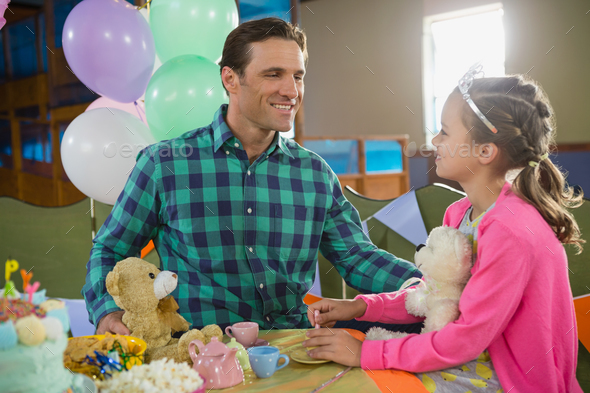 Father and girl interacting while playing toy kitchen set - Stock Photo - Images