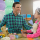 Father and girl interacting while playing toy kitchen set - PhotoDune Item for Sale