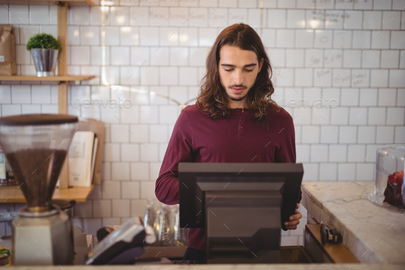Young waiter with long hair using cash register at coffee shop - Stock Photo - Images