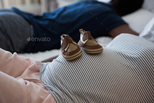 Pregnant woman relaxing with baby shoes on her belly in bedroom - Stock Photo - Images