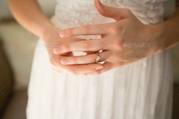 Midsection of bride wearing wedding ring at home - Stock Photo - Images