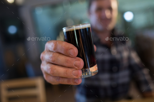 Close up of man holding beer glass at bar - Stock Photo - Images