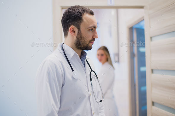 Sad pensive doctor staying in hospital corridor - Stock Photo - Images