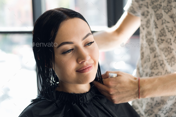 Unrecognizable hairdresser creating hairstyle for beautiful brunette woman - Stock Photo - Images
