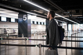 Young man with his luggage and backpack using smartphone while waiting for airline flight in the - PhotoDune Item for Sale