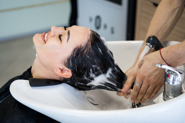 Haircare procedure in beauty salon. Hairdresser is brushing woman's hair spreading a treatment - Stock Photo - Images