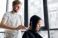 Young beautiful woman having her hair cut at the hairdresser's. Young male hairdresser smiling - PhotoDune Item for Sale
