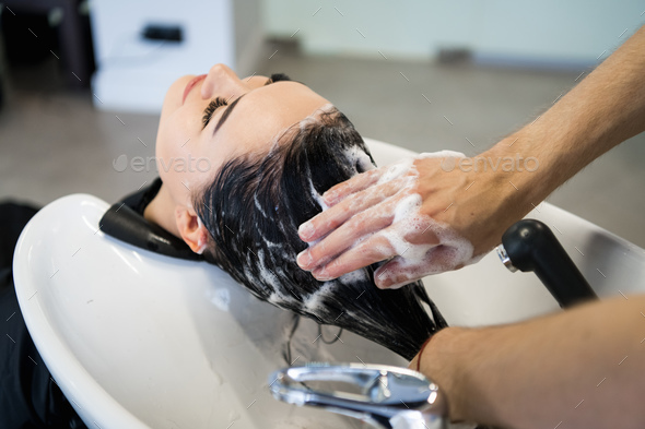 Female client getting hair washed by hairstylist in parlor - Stock Photo - Images